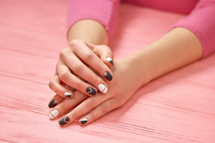 mani di donna con smalto su sfondo rosa