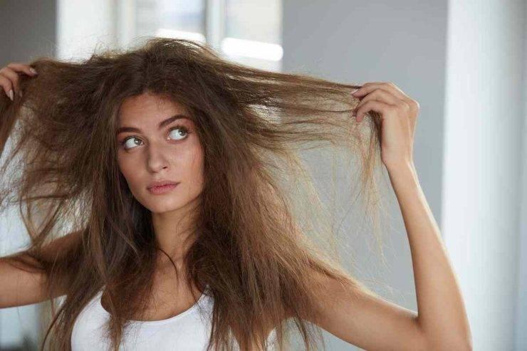 donna che tocca i suoi capelli secchi