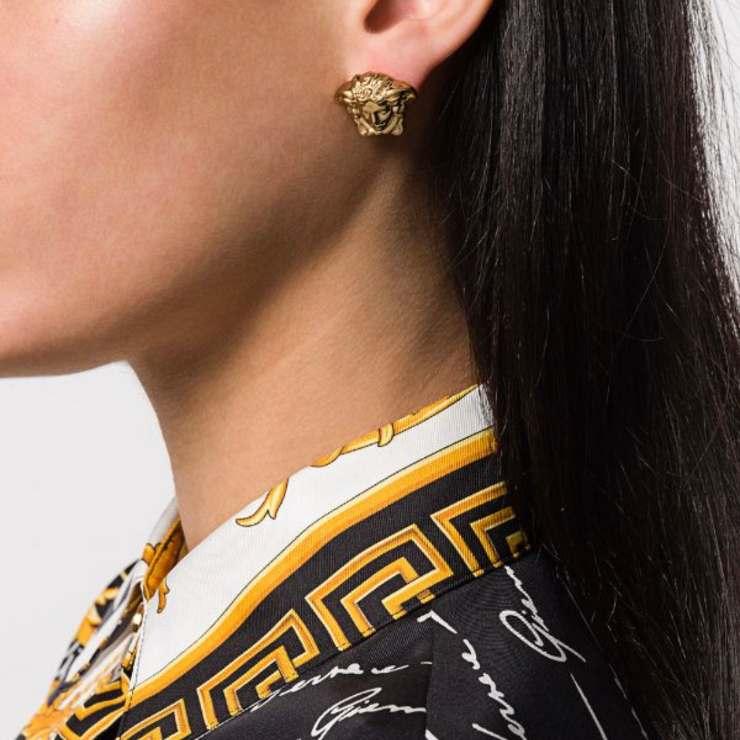 Orecchini Medusa di Versace dorati effetto lucido.
