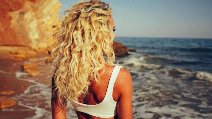 donna con capelli ricci biondo in riva al mare
