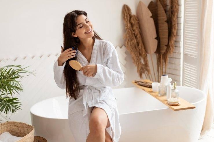 donna che si pettina capelli in bagno