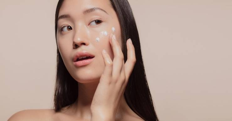 donna asiatica applica crema viso