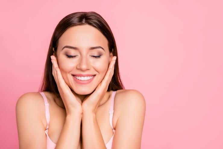 donna che si accarezza il viso su fondo rosa
