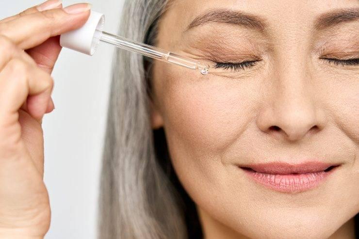donna matura applica siero contorno occhi