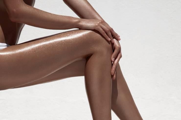 gambe abbronzate su fondo bianco
