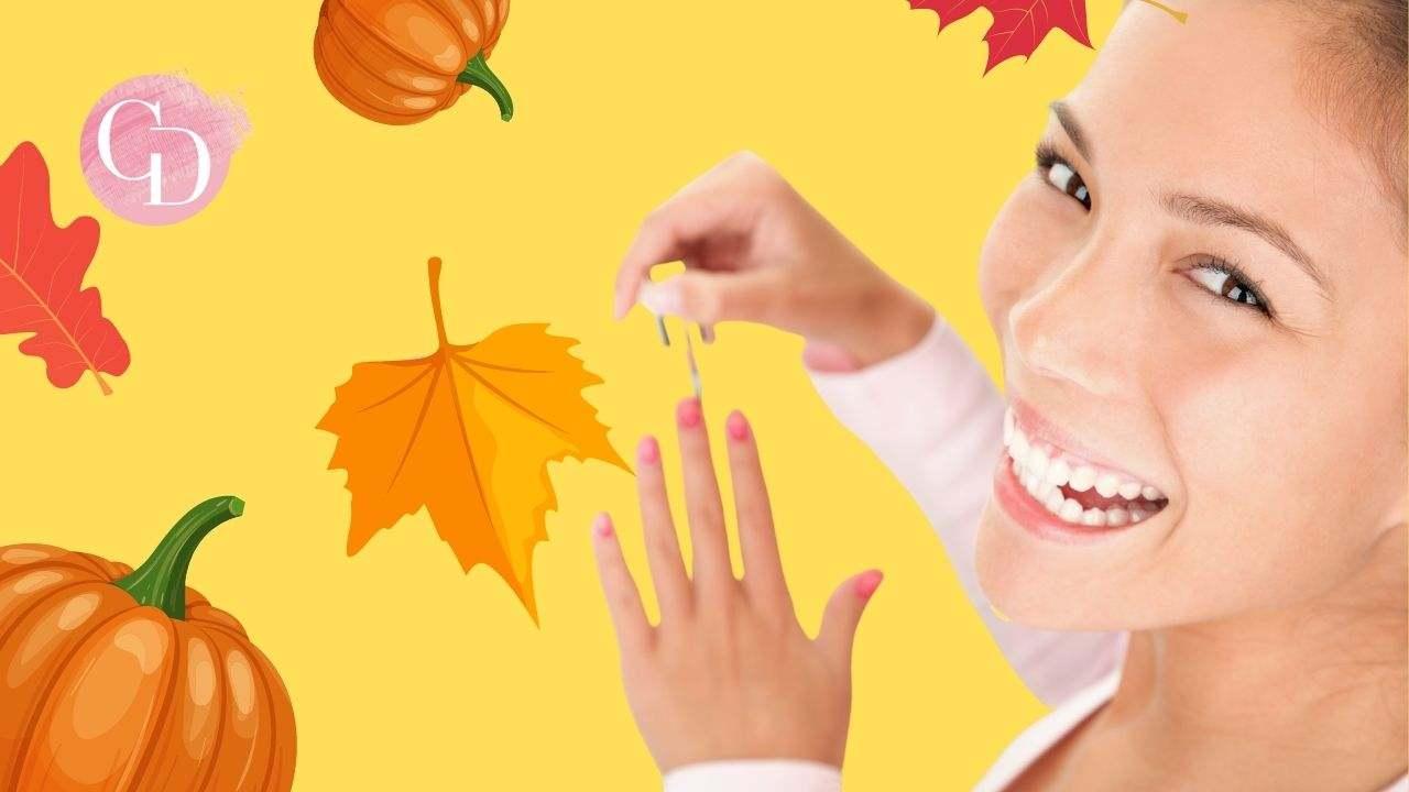 nail art autunnale ragazza che mette lo smalto alle unghie e sorride
