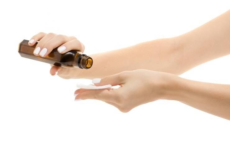 struccare il mascara mani che applicano olio su dischetto di cotone