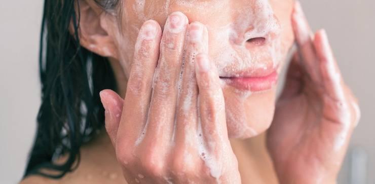 detergente per la pelle del viso donna che si lava il viso